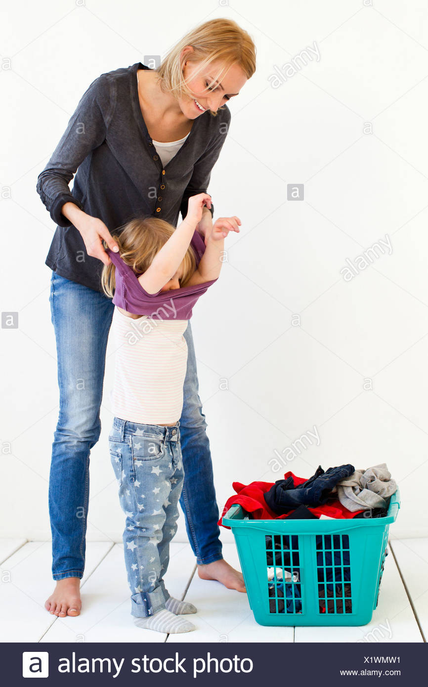 Studio shot of mother taking off daughter's clothes for laundry - Stock Image
