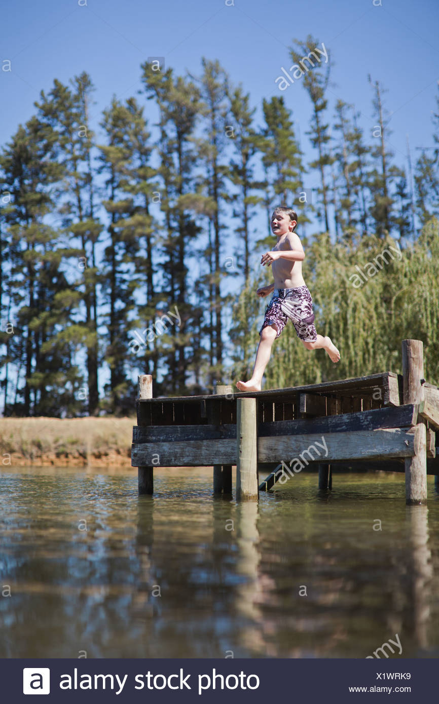 Boy jumping into lake from jetty Stock Photo