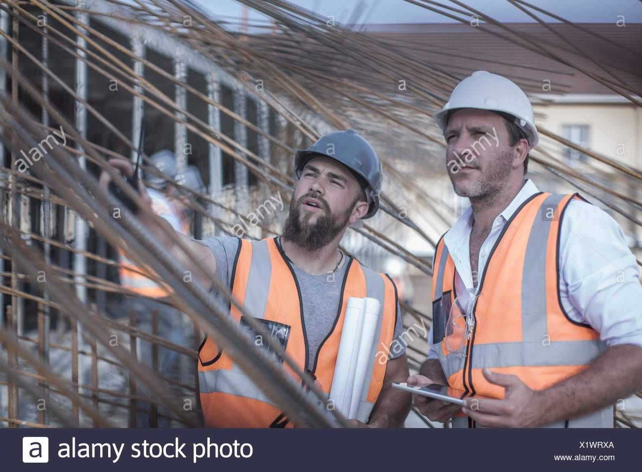 Site manager and builder discussing steel rod structures on  construction site - Stock Image