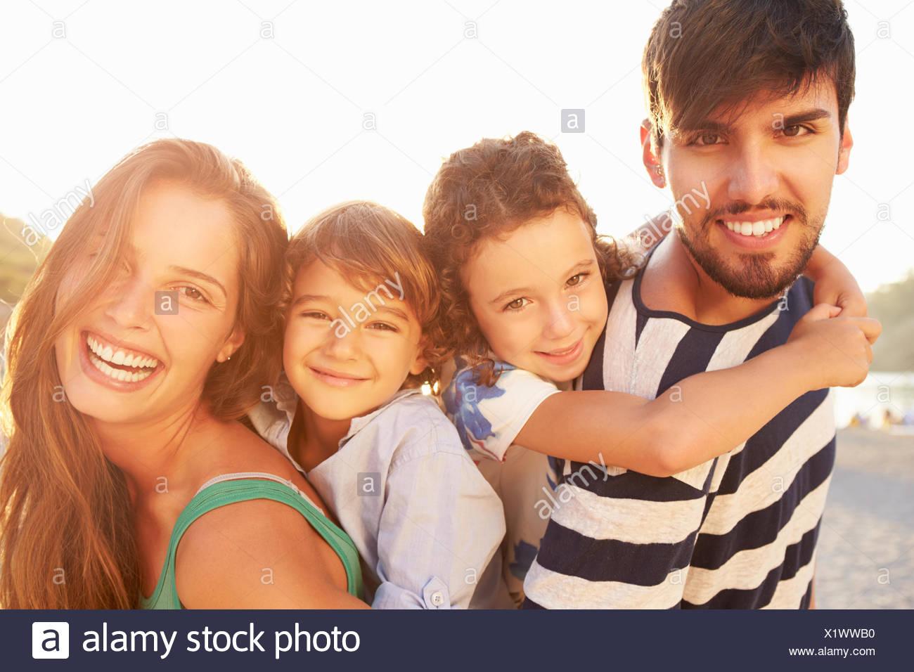 Parents Giving Children Piggybacks On Summer Holiday - Stock Image