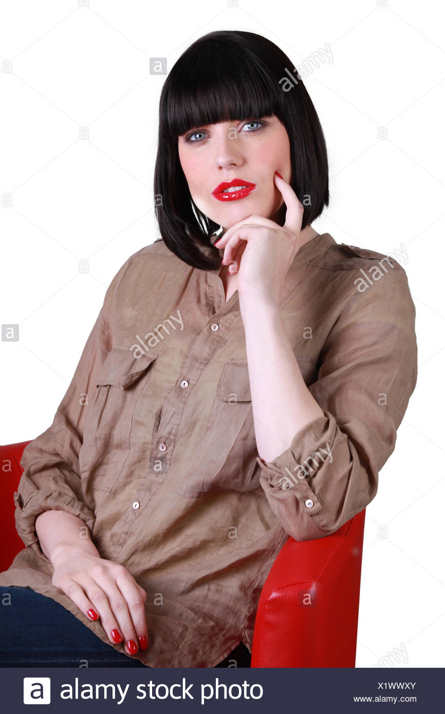Woman sitting in a red chair - Stock Image