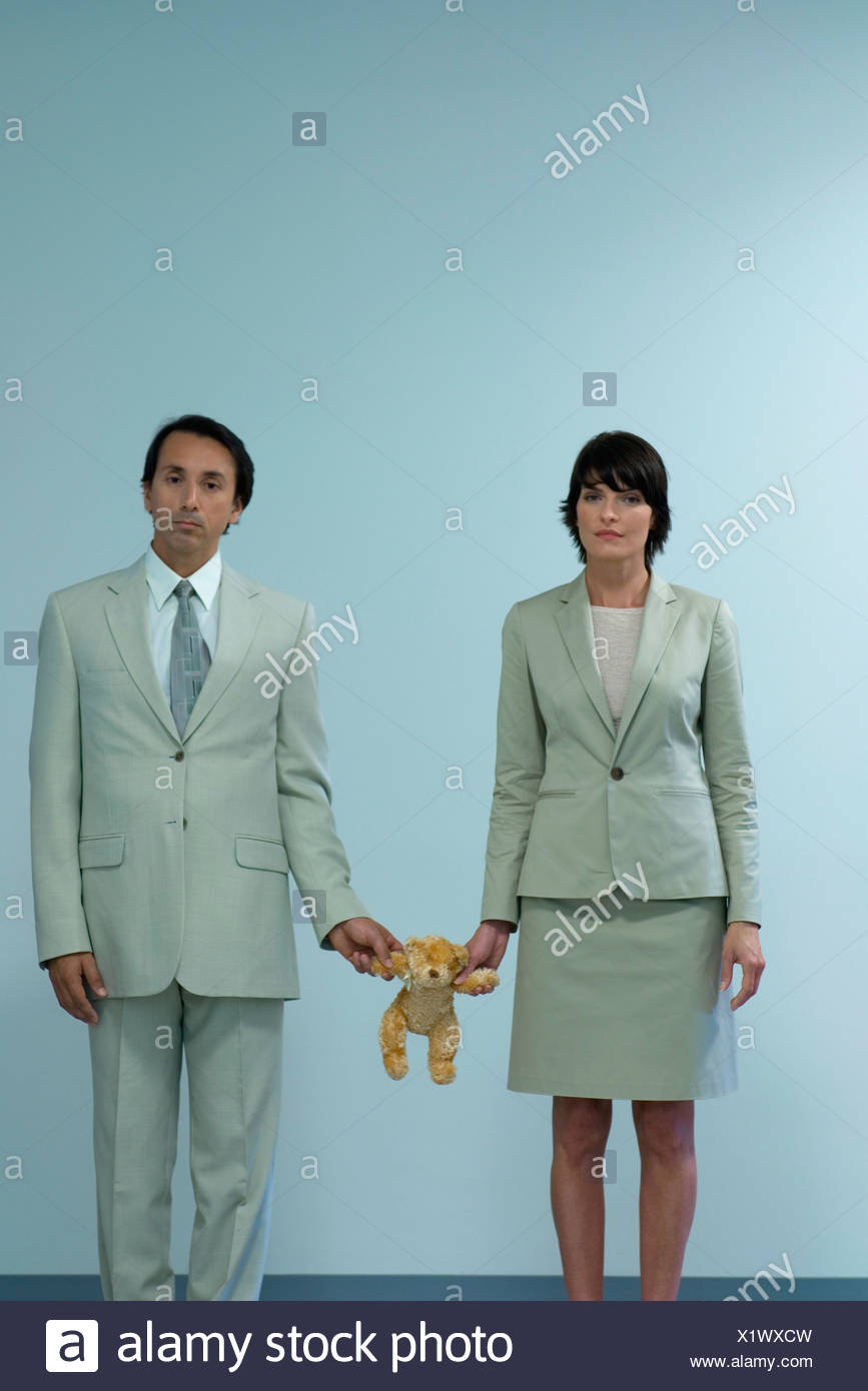 Professional couple standing together holding teddy bear between them - Stock Image