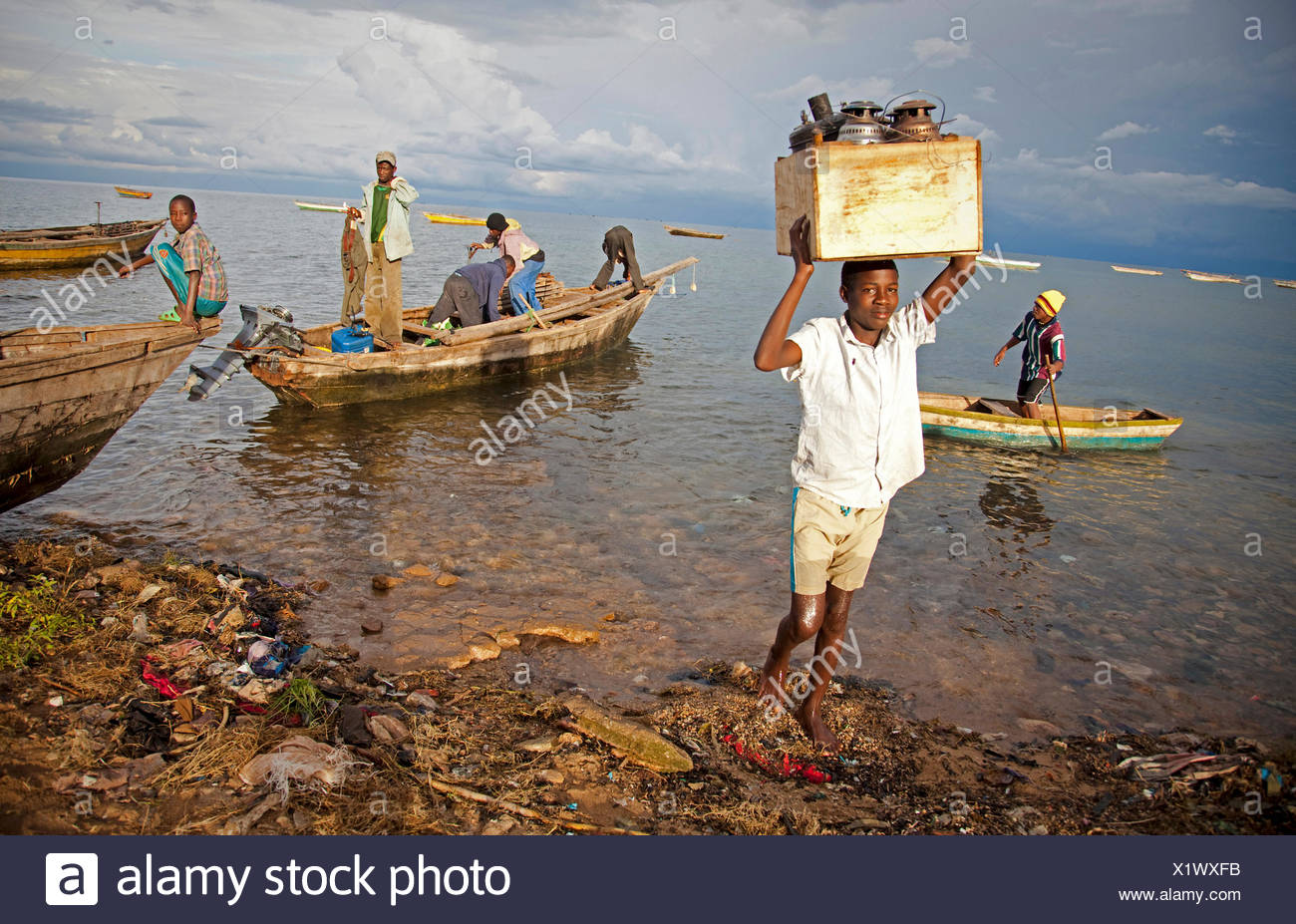 a boy carrying a box with oil lamps from fishing boat, Lake Tanganyika, Burundi, Makamba, Mvugo, Nyanza Lac - Stock Image