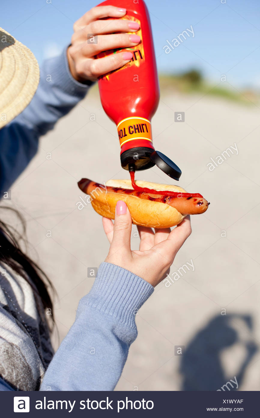 Cropped image of woman putting chili sauce on hot dog - Stock Image