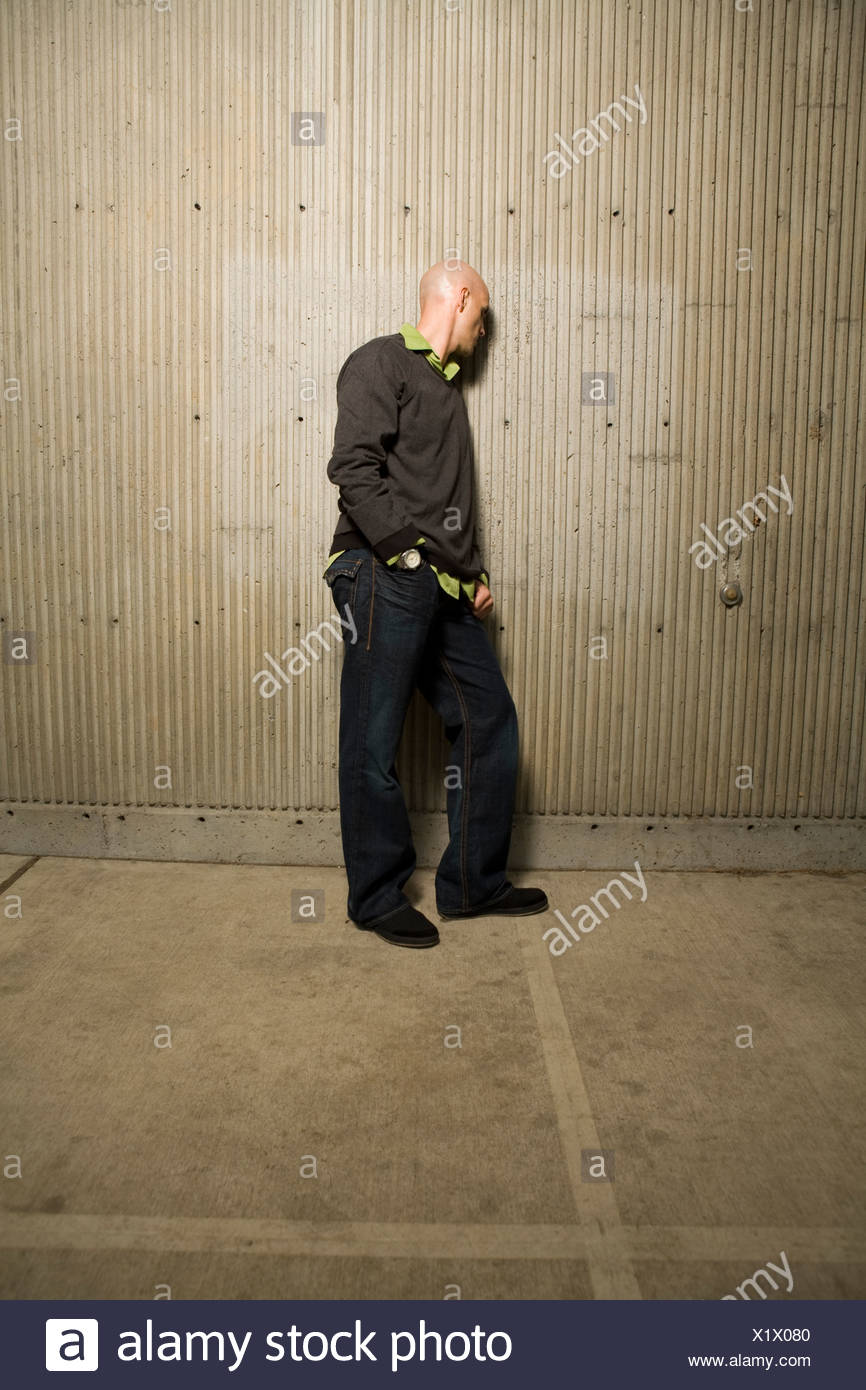Full length image of man turned to face a cement wall - Stock Image