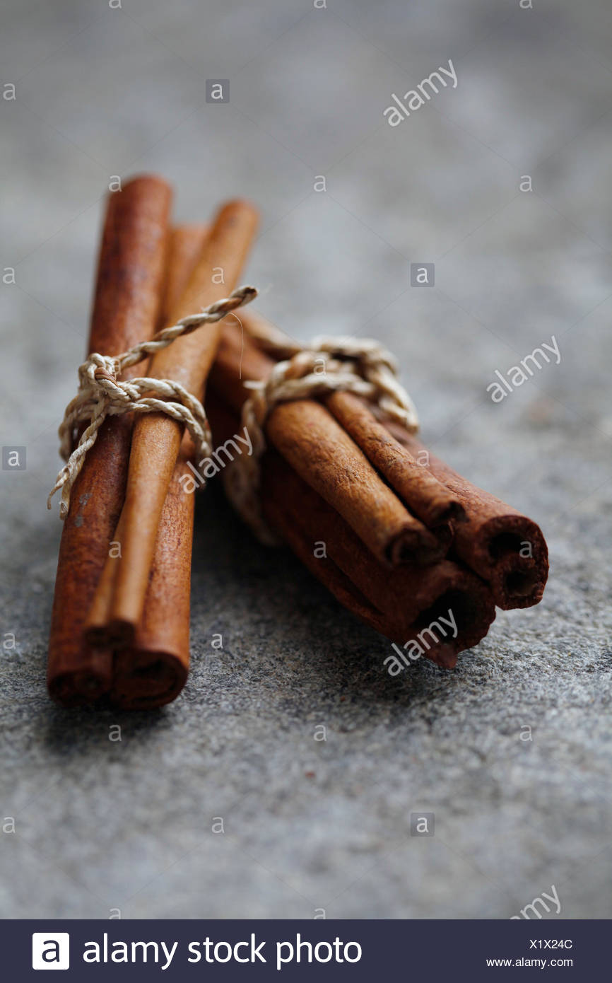 two bundles of cinnamon on a stone surface - Stock Image