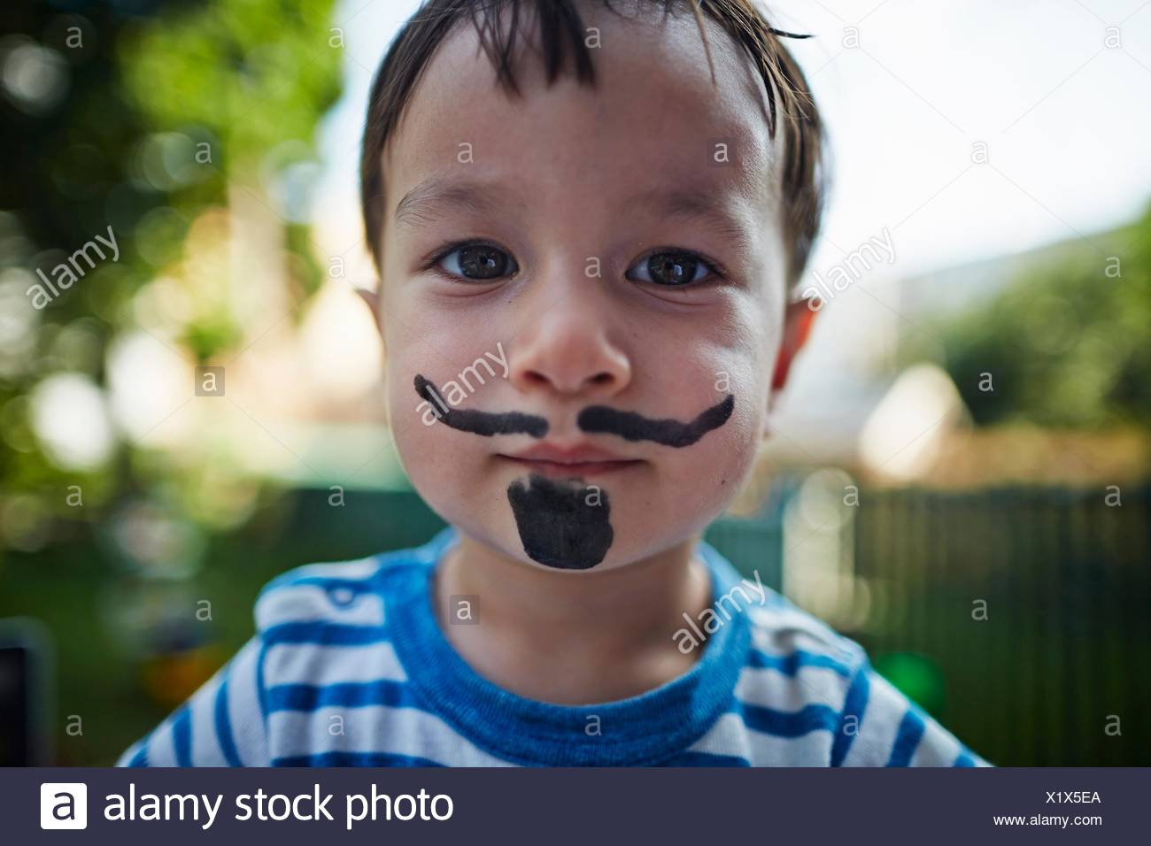Close up portrait of boy looking at camera wearing beard and moustache face paint costume - Stock Image