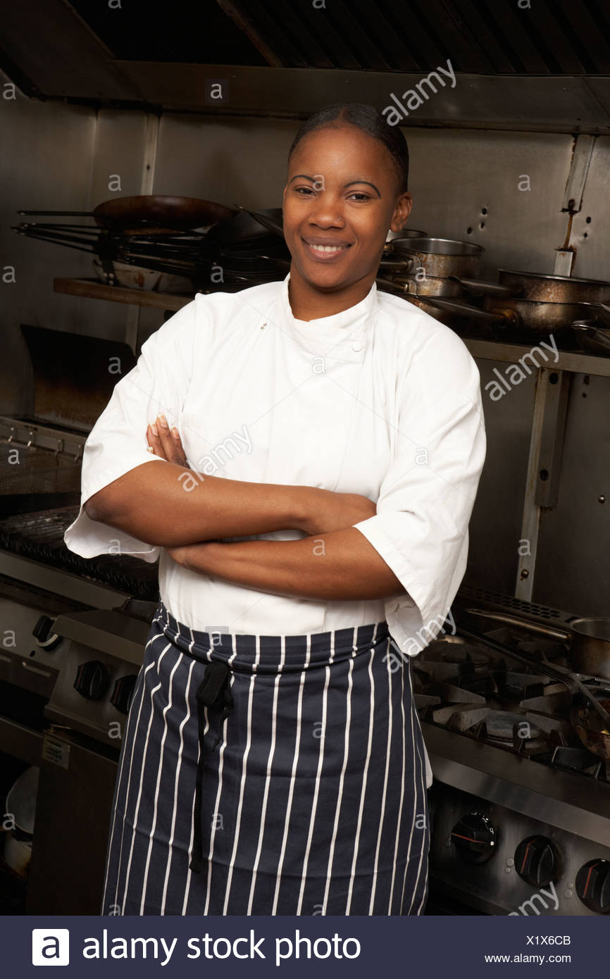 Female Chef Standing Next To Cooker In Restaurant Kitchen - Stock Image