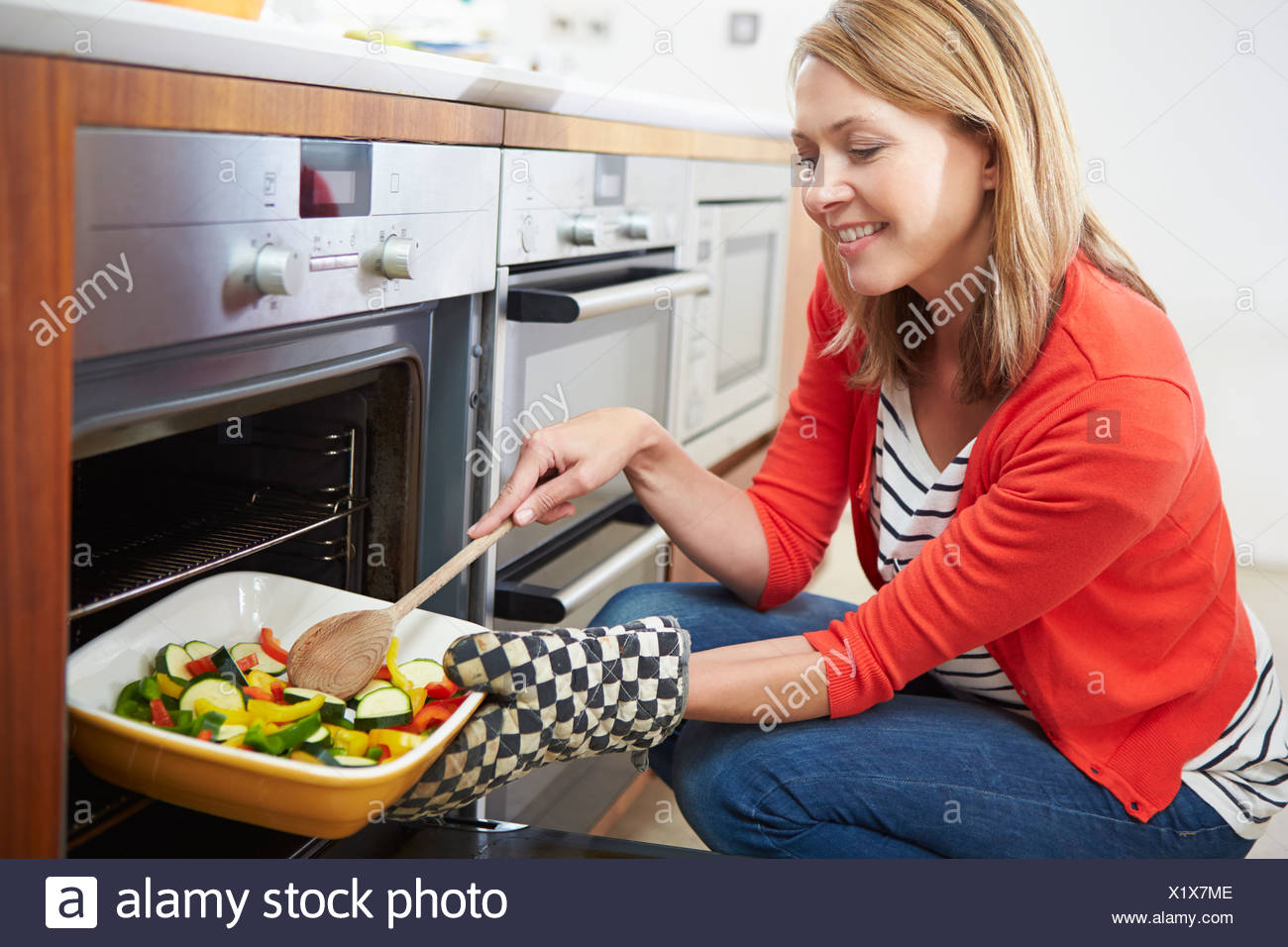 Woman Putting Tray Of Roast Vegetables Into Oven - Stock Image