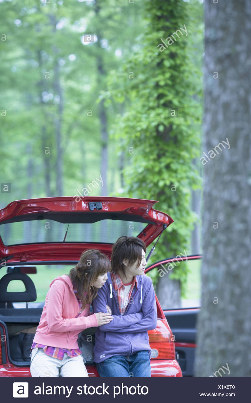Young Couple Sitting on Vehicle Trunk and Chatting - Stock Image
