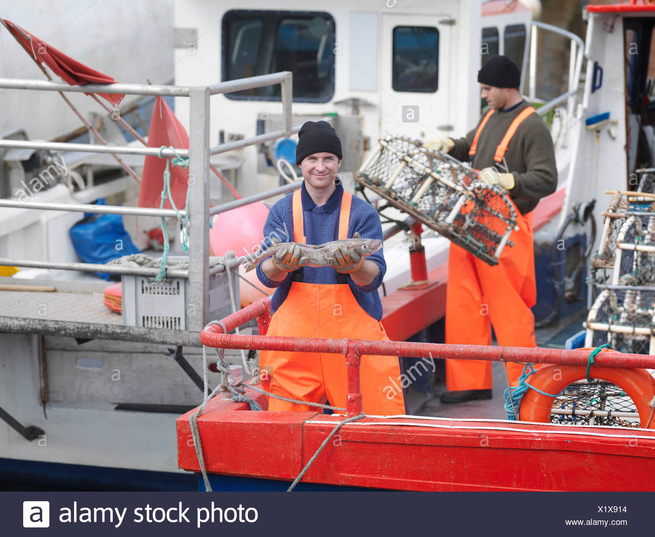 Fisherman holds fish on boat in harbour - Stock Image
