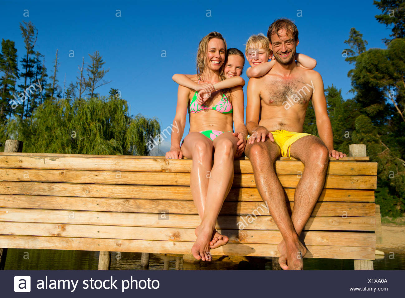 Portrait of happy family sat on jetty beside lake - Stock Image