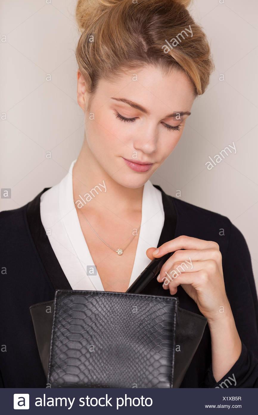 Beautiful woman checking her makeup bag - Stock Image