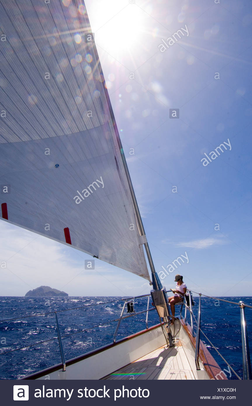 Relaxing in the sun on the bow of SY 'Adele', 180 foot Hoek Design, whilst sailing from Antigua to Nevis - Stock Image