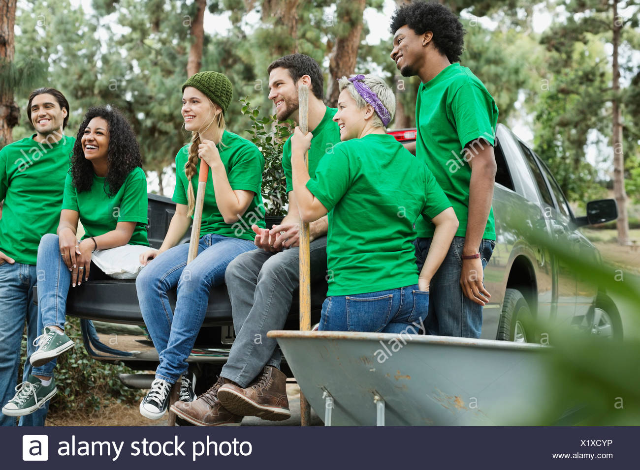 Group of happy clean up crew sitting on tailgate - Stock Image