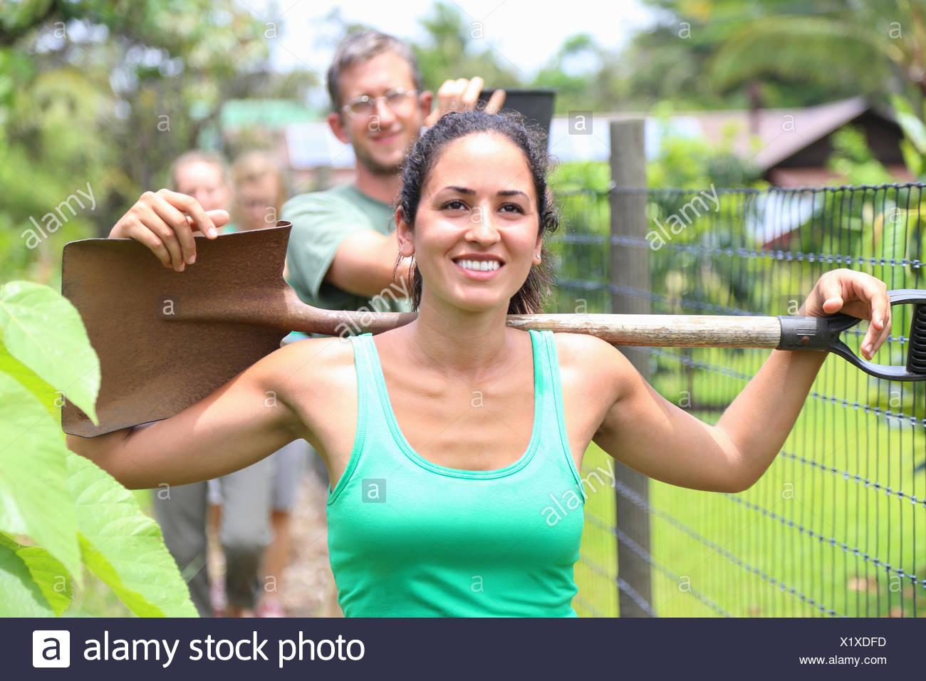 Smiling woman wearing green tank top carrying shovel on shoulders through community garden - Stock Image