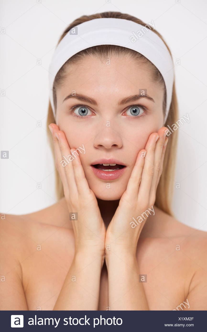 Beautiful woman looking surprised - Stock Image