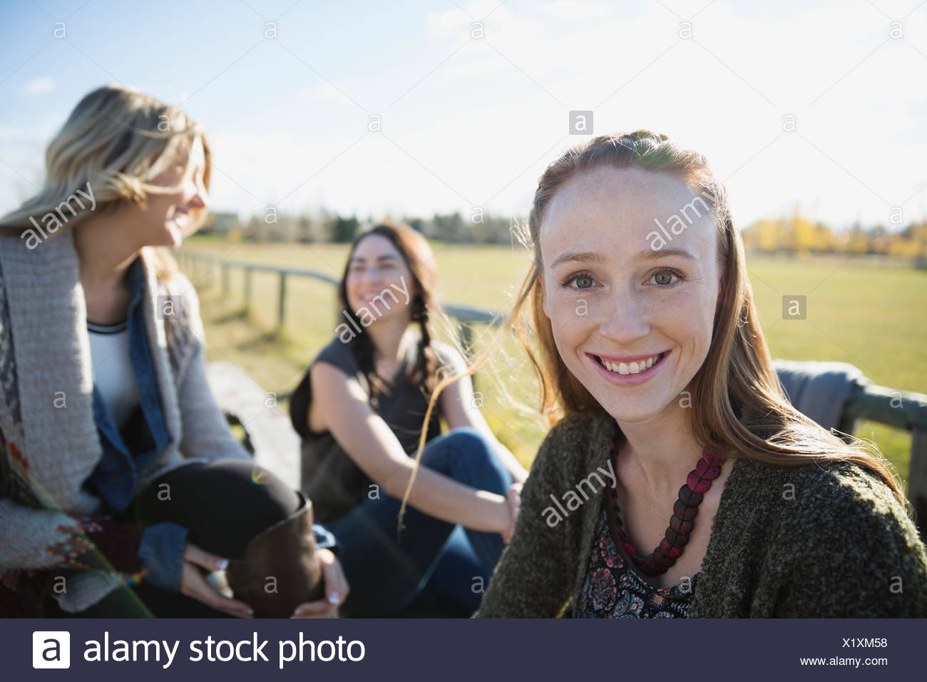 Portrait smiling young woman with friends in park Stock Photo