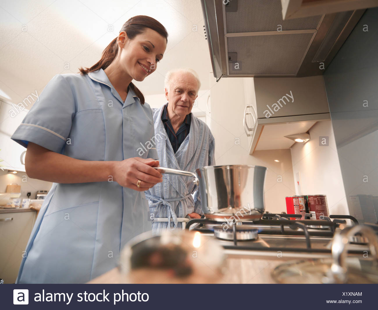 Nurse cooking for older man in kitchen Stock Photo