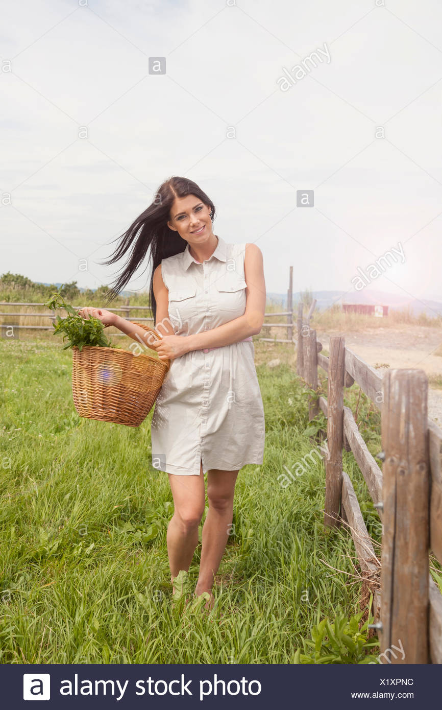 Young woman with basket of vegetable on field, Roznov, Czech Republic - Stock Image