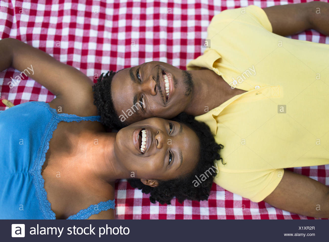 Overhead portrait of young couple lying on picnic blanket on opposite sides - Stock Image