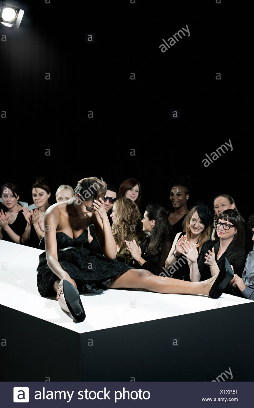 Model sitting on catwalk having fallen down at fashion show - Stock Image