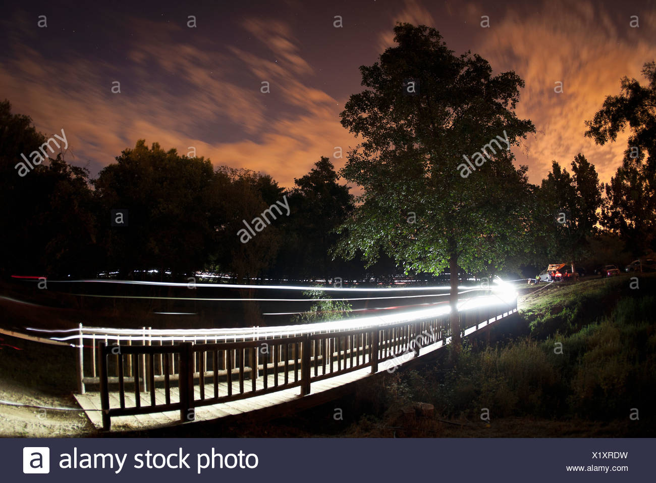Trails of light from mountain bikers - Stock Image
