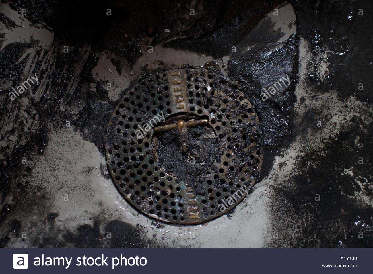 closed sewage lid. unhygienic, cloudburst, messy, manhole. - Stock Image