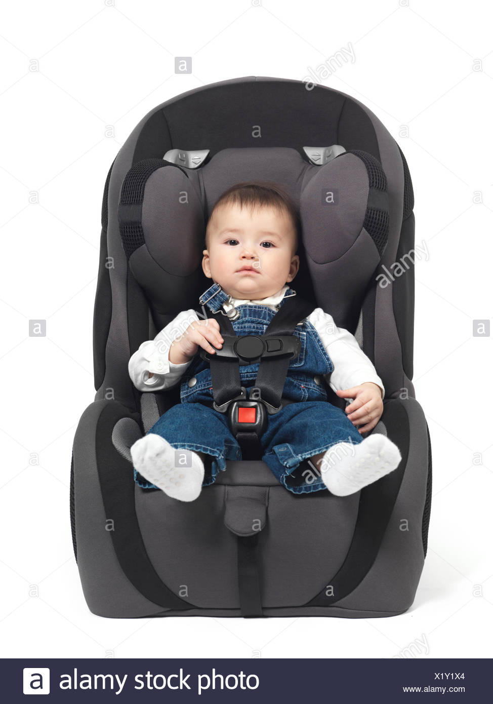 Baby sitting in a child safety seat - Stock Image