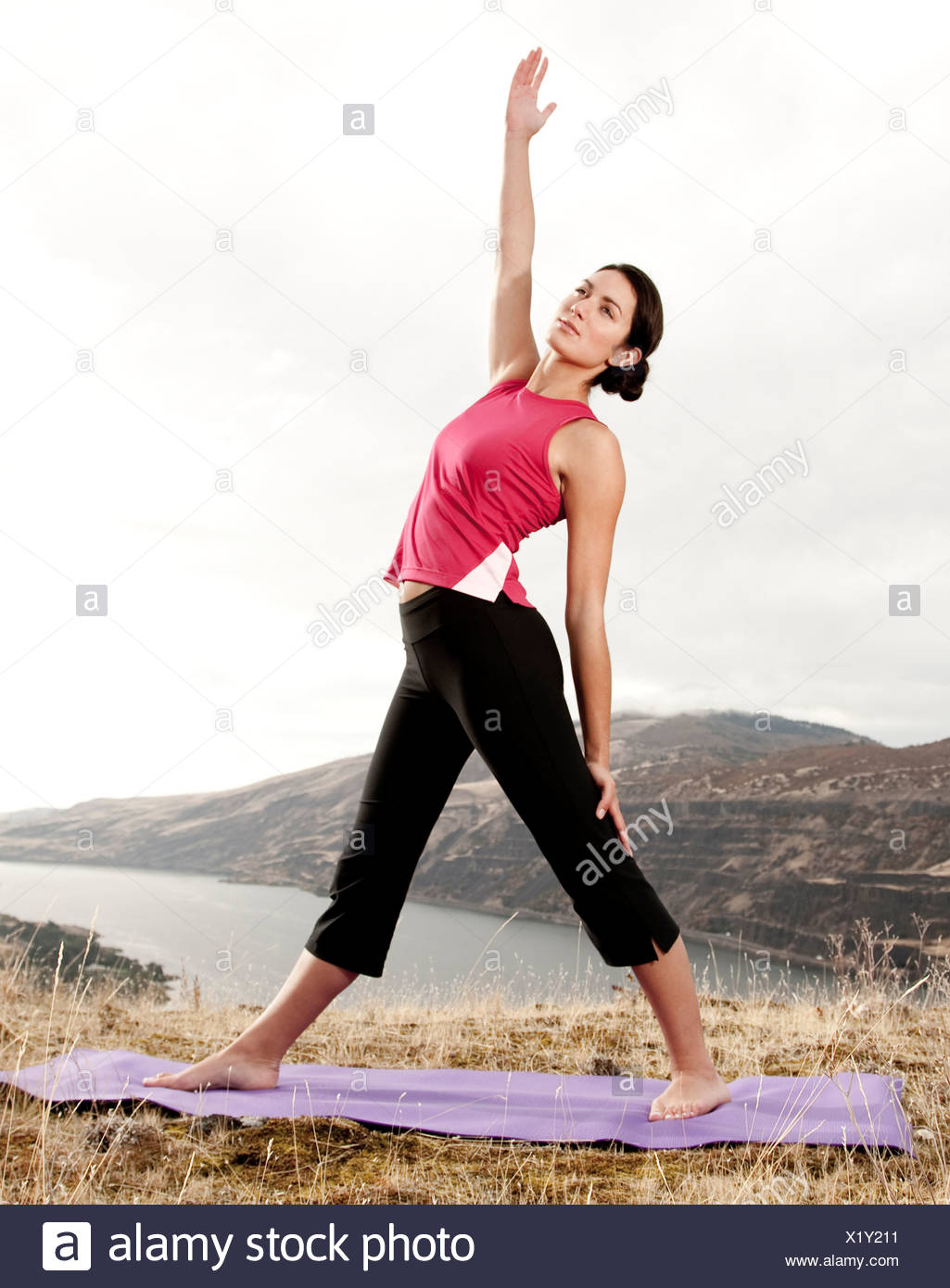 A female practicing yoga in the outdoors with the Columbia River Gorge in the distance. Stock Photo