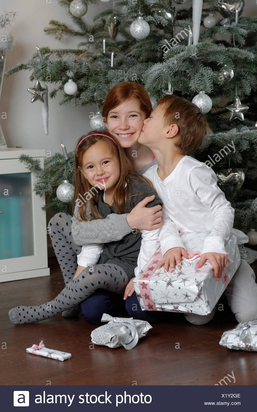 Christmas Eve, happy siblings with Christmas presents under the Christmas tree, Bavaria, Germany - Stock Image