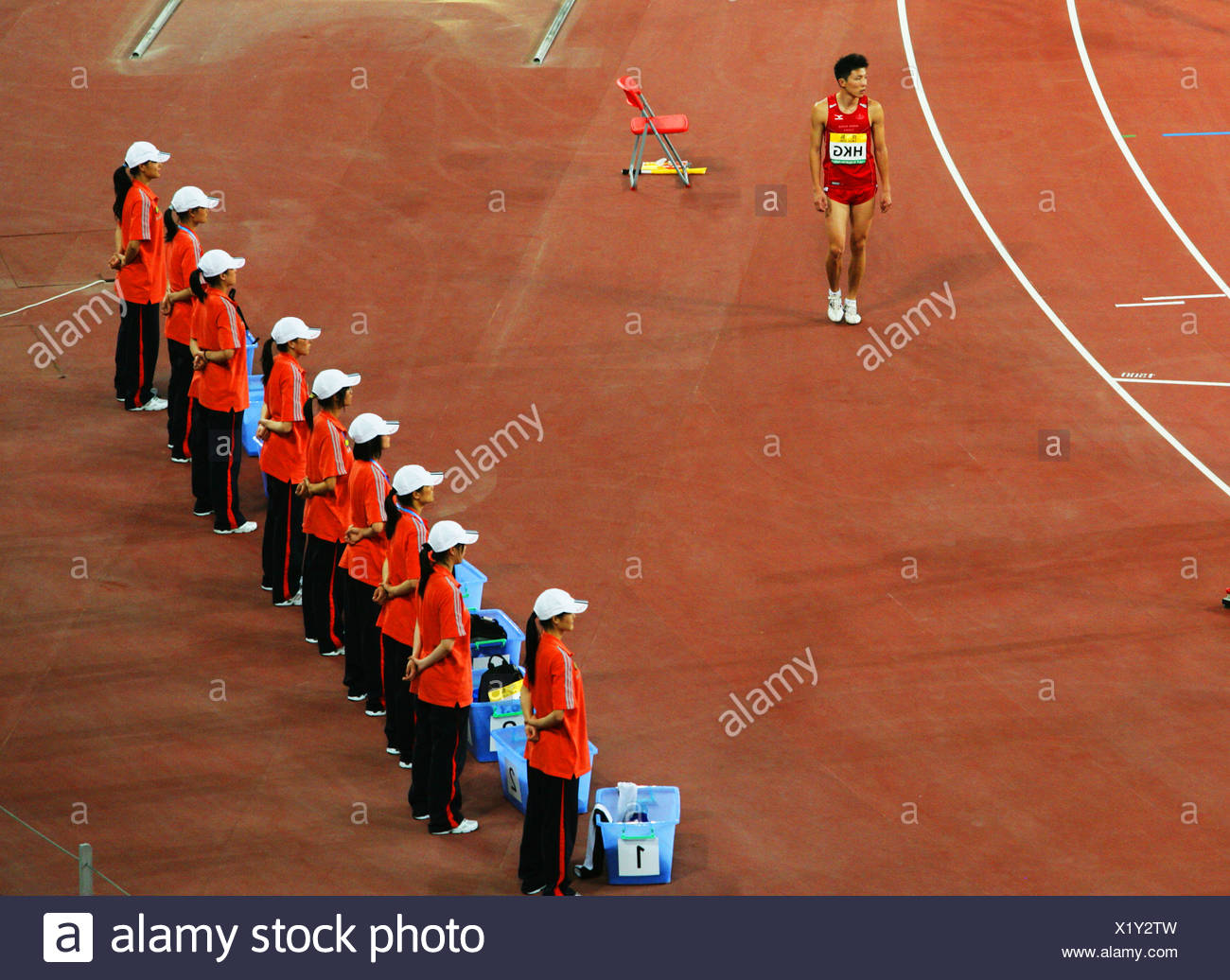 An athelete from Hong Kong walks pass a row of janitors, Beijing, China - Stock Image