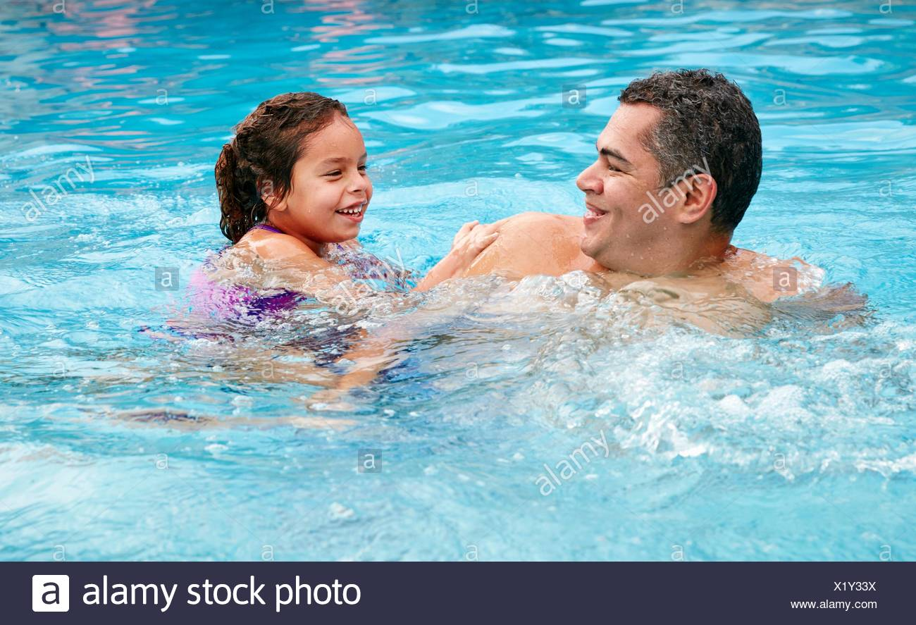 Head and shoulders of father and daughter in swimming pool smiling - Stock Image