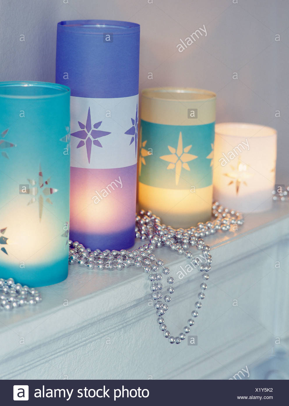 Close-up of etched glass candle holders with lighted candles - Stock Image