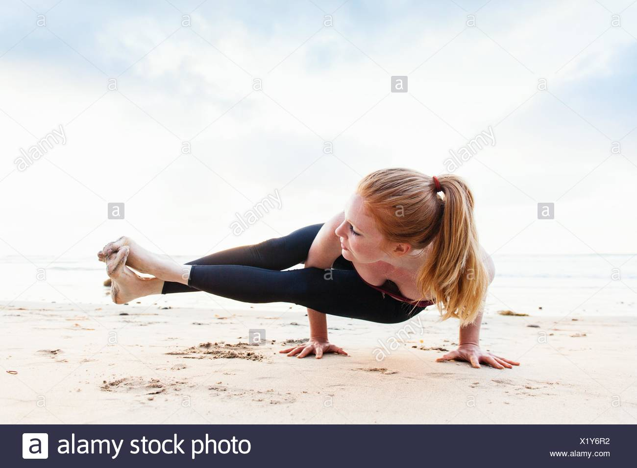 Mid adult woman poised in yoga position on beach - Stock Image
