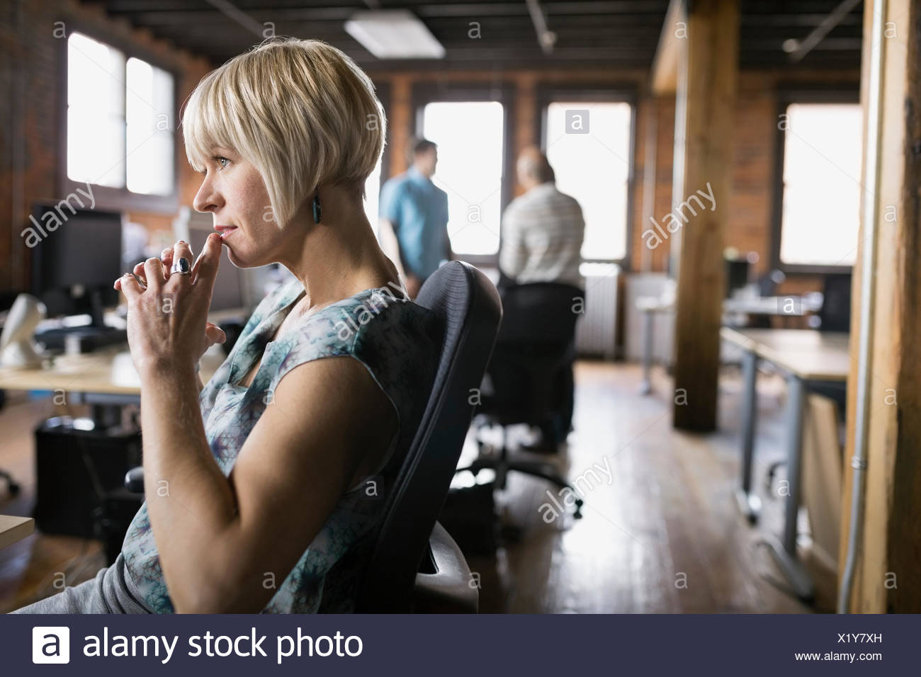 Pensive businesswoman looking away in office - Stock Image