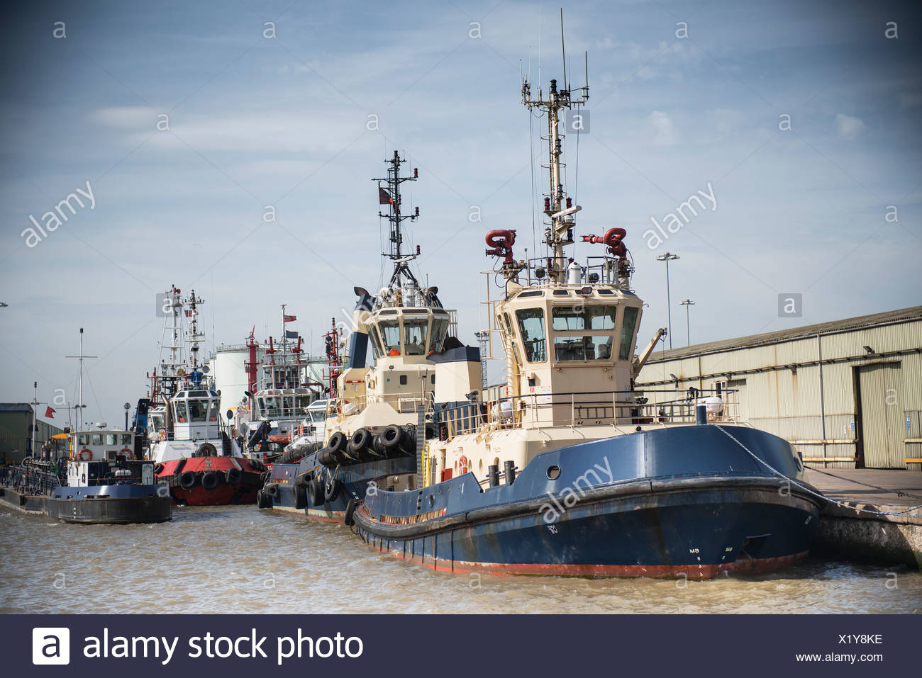 Tug boats docked in urban harbor - Stock Image