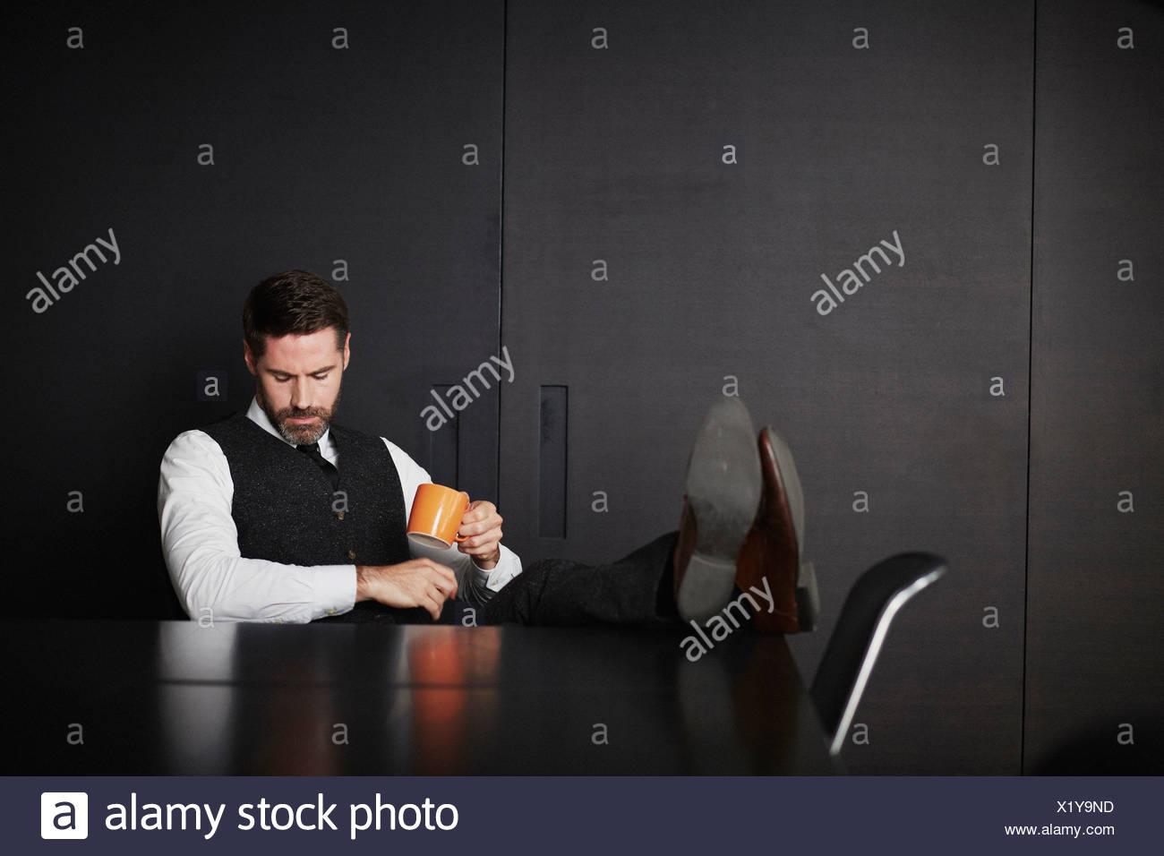 Businessman with feet up holding coffee - Stock Image