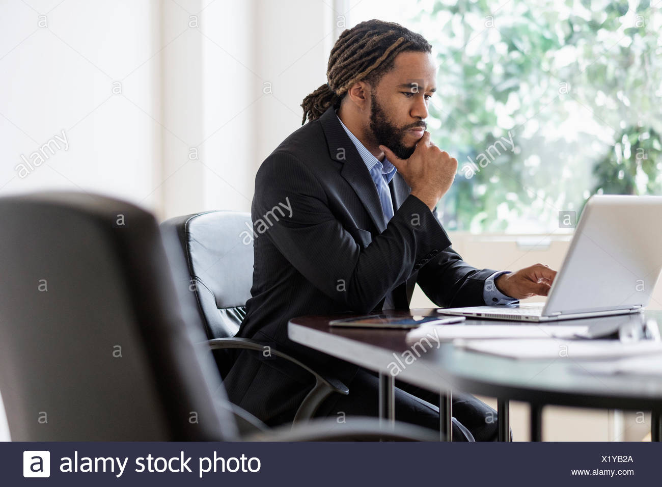 Concentrated businessman working with laptop at desk in office - Stock Image