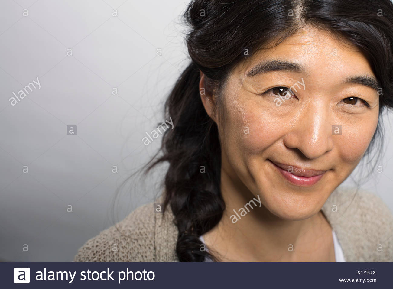 Close up of smiling woman with braided hair - Stock Image