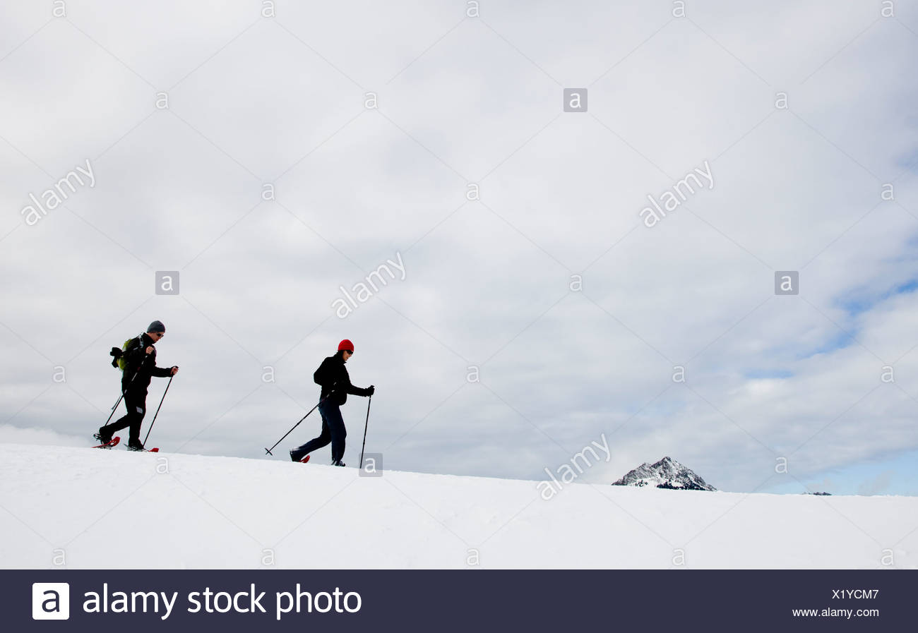 Two people snow shoeing along a ridge on an overcast day. - Stock Image