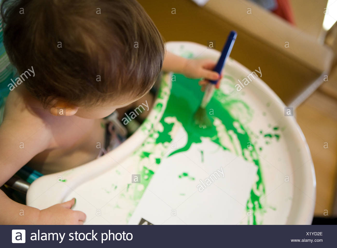 Baby boy in high chair with green paint - Stock Image