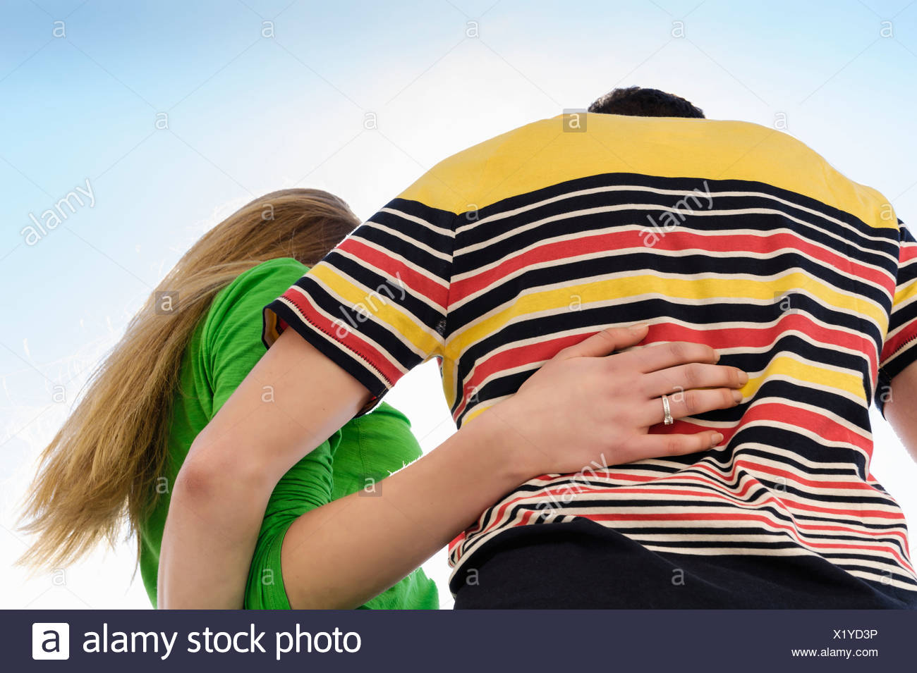 Couple with arms around each other against sky, low angle - Stock Image