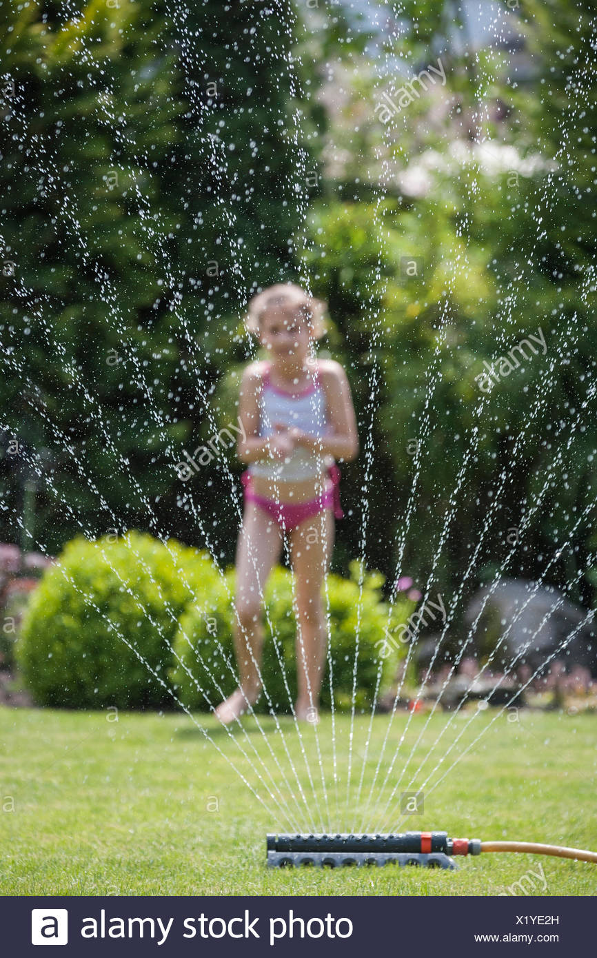 Girl behind sprinkler in garden - Stock Image