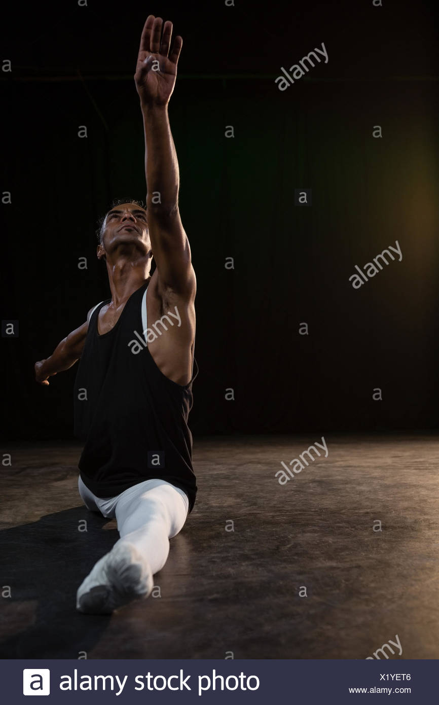 Ballet dancer performing a split in the stage - Stock Image