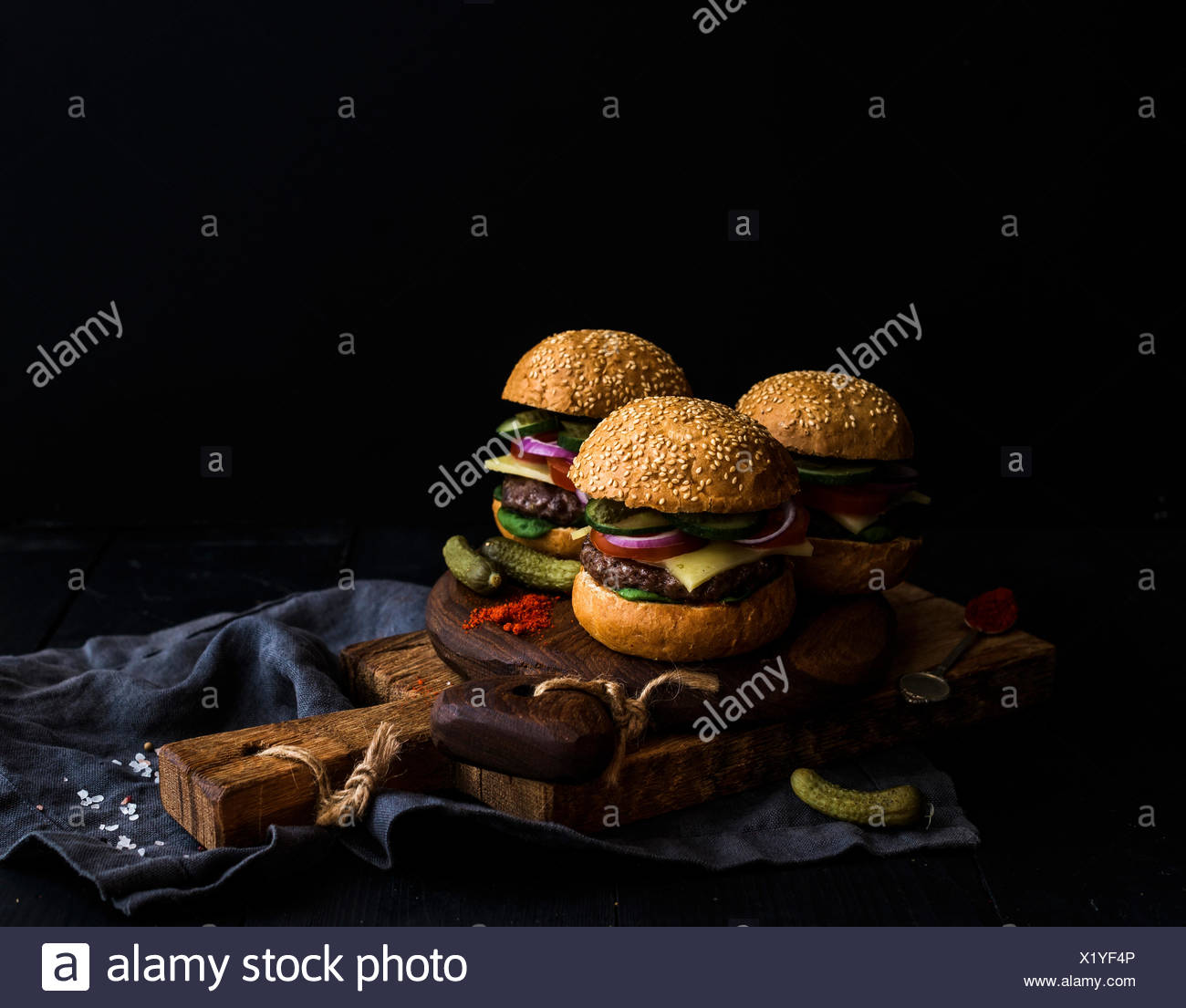 Fresh beef burgers with cheese, vegetables, pickles and spicy tomato sauce on paper on rustic wooden boards, black background, s - Stock Image