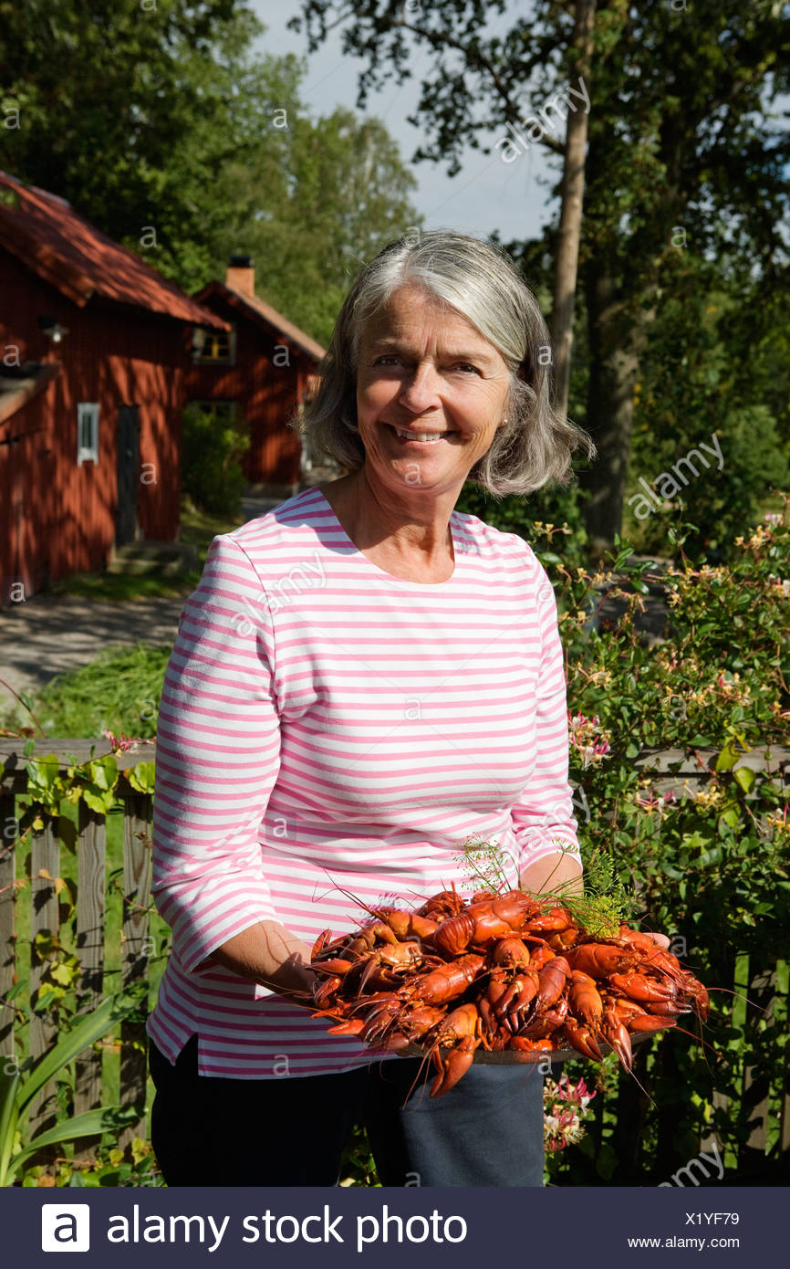 Senior woman holding plate of cray fish in garden - Stock Image