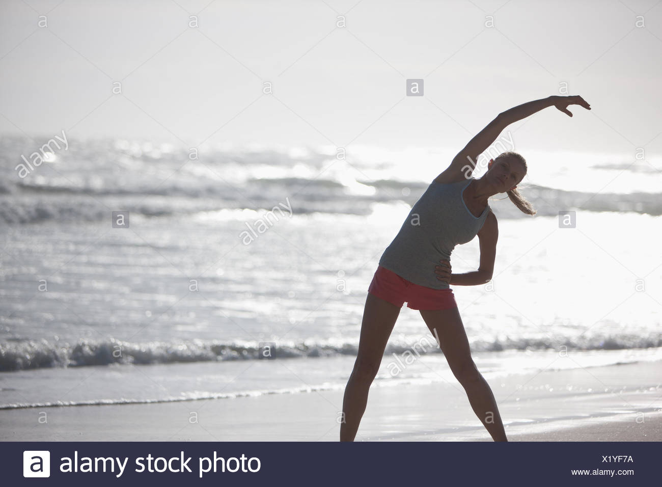 Woman stretching on beach - Stock Image