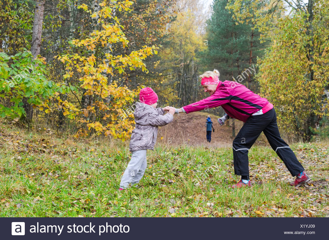 Woman with girl doing aerobics in the autumn park - Stock Image