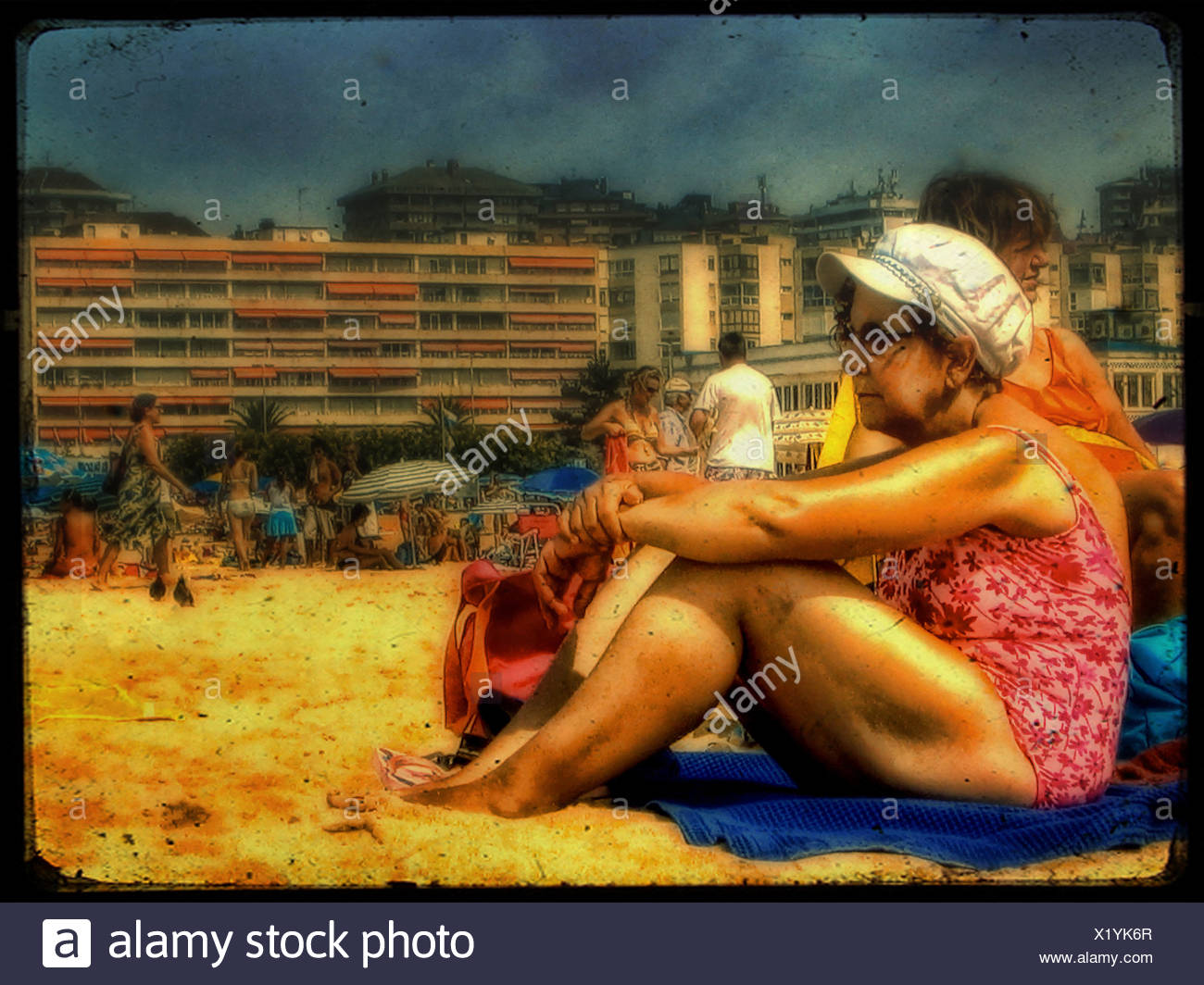 An old woman wearing a bathing costume and white hat sitting on a beach with hotels in the background - Stock Image